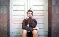 Portrait of a young man sitting in front of a door on the stairs