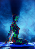 Girl with bright patterns on body posing in smoke