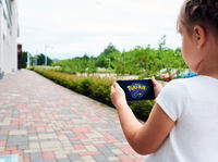 Little girl playing a Pokemon Go game outdoors.