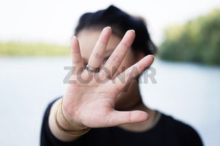 woman hiding face behind hand