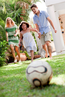 Cute girl rushing towards football as her brother and mom follow her