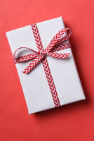 White paper wrapped Christmas present with red ans white ribbon on a red background.