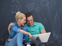 couple using laptop in front of gray chalkboard