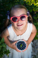 Little girl in sunglasses holding a bowl of blueberries - shallow depth of field - top view