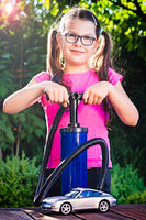Girl playing with a car  - adding air pressure - pumping air into auto wheel. vehicle safe concept