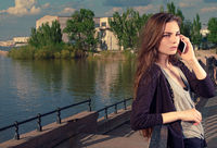 Young woman talking on her mobile phone listening to the conversation with a serious expression, she stands outdoors on granite embankment against a river