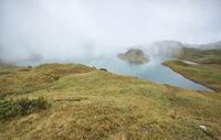 alpine lake in dense autumn fog