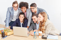 Internet Start-Up Team schaut zusammen auf Laptop