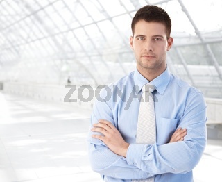 Confident businessman standing at modern passage