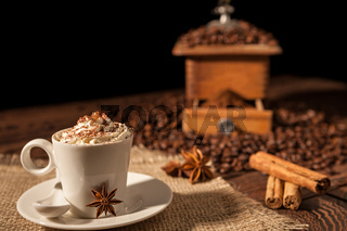 Coffee cup with whipped cream, cocoa powder and star anise