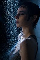 Brunette in wet t-shirt under water profile view