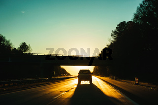 Car driving into the sunset