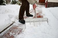 Mann beim Schneeschippen auf Fußweg