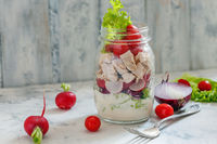 Salad with chicken and fresh vegetables in jar.