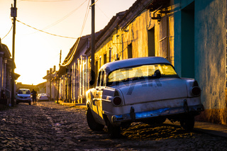 Trinidad, Cuba: Street with oldtimer at sunset