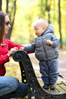 One year old baby boy in autumn park with his mother
