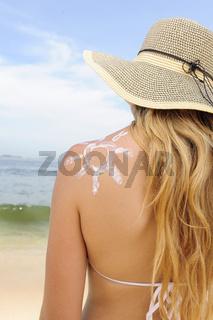 Frau mit Sonne aus Sonnencreme auf der Schulter betrachtet das Meer