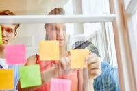 Geschäftsleute machen Notizen auf Zetteln