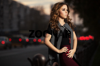 Young fashion woman with long curly hairs on night city street