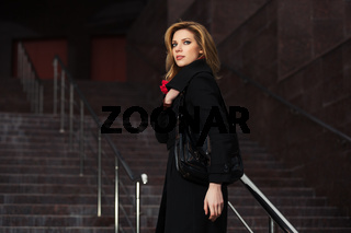 Fashion blond woman in black coat on the steps