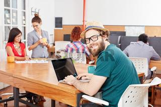 Junger Student und Nerd am Laptop