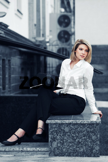 Young blond business woman with a folder