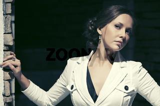 Sad beautiful fashion woman in white jacket in a night city street