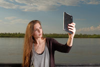 Beautiful young adult woman taking picture of herself, selfie shot with phablet leaning back metal fence in front of river
