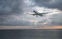 Airplane flying above the sea over cloudy sky
