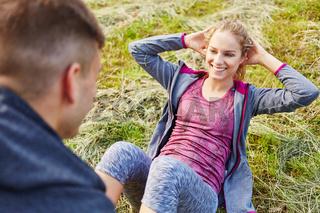Mann hilft Frau bei Sit-ups
