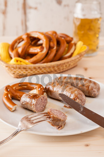 Closeup of bavarian cooked sausage and pretzel