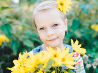 Little girl with a bouquet of yellow wildflowers in a meadow