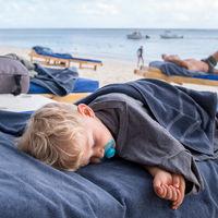 infant boy sleeping on the beach
