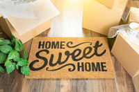 Home Sweet Home Welcome Mat and Moving Boxes on Hard Wood Floor
