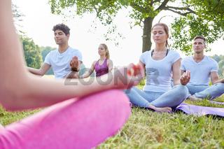 Junge Leute meditieren in einem Kurs