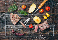 Delicious grilled beef steak with seasoning on wooden background