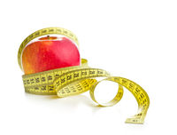 Fresh red apple and measuring tape.
