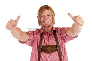 Lachender Mann in Oktoberfest Lederhose zeigt beide Daumen nach