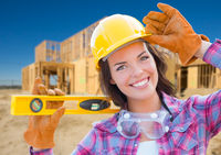 Female Construction Worker Holding Level Wearing Gloves, Hard Hat and Protective Goggles at Construction Site