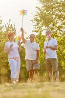Drei Senioren halten Windrädchen