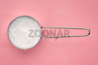 coconut cooking oil  in a measuring scoop
