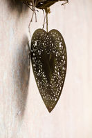 Metal heart is hanging on a house wall