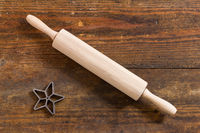 Rolling pin and baking pan star on weathered wooden board