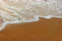 Foamy wave of warm tropical sea on beach top view