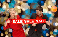 couple with red sale sign over christmas lights