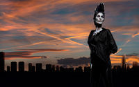 Woman with a creative chess figures make-up against Benidorm skyline. Spain