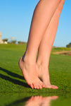 beautiful female legs on grass near lake