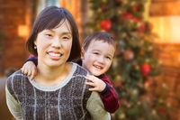 Chinese Mother and Mixed Race Child Inside House In Front of Decorated Christmas Tree.