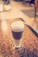Latte coffee in glass on rare wood table, selective focus, colorized vintage shot,shallow DOF