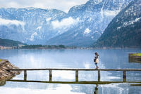 Girl walking on a deck over an alpine lake